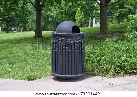 Park trashcan along pathway with green grass in background. #1735014491