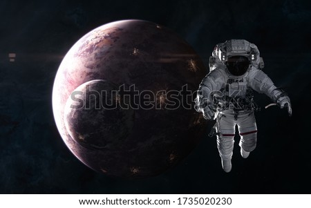 Astronaut on background of inhabited planets in red light. Deep space. Science fiction. Elements of this image furnished by NASA