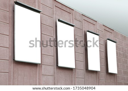 Blank banners on building facade outdoors. Advertising board design