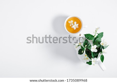 Jasmine flowers and teapot on white background. Herbal tea of jasmine flower. Jasmine tea concept. Flat lay, top view, copy space #1735089968