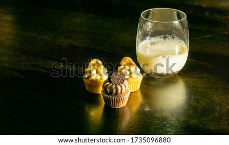 Three cute mini cupcakes and a glass of milk are on the wooden background. Dark tone picture of dessert and snack with copy space.