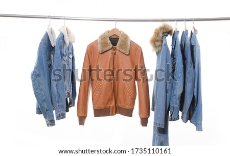Row of  fashion jeans jacket and jeans shirtswith long coat  and brown leather jacket on hangers     #1735110161