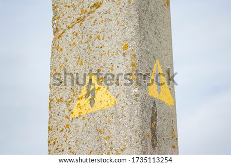 part of an old concrete pillar of a power line with a picture in the form of a yellow triangle with a lightning