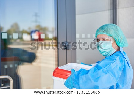 Doctor or surgeon with organ transport after organ donation for operation in front of the clinic entrance in protective clothing Royalty-Free Stock Photo #1735155086