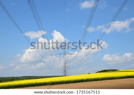 Power line over an idyllic spring landscape with rapeseed fields #1735167515