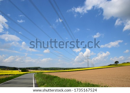 Power line over an idyllic spring landscape with rapeseed fields #1735167524