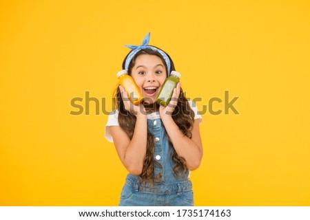Hand crafted smoothie recipe. Fruit energy. Smiling kid hold smoothie bottles. Healthy food. Vitamin nutrition. Fresh smoothie. Girl drinking orange fresh juice smoothie. Vegetarian concept. #1735174163