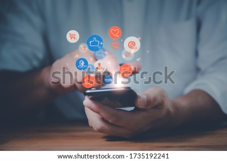 Social media interactions on mobile phone, concept with notification icons of like, message, email, comment and star above smartphone screen, person hands holding device, internet digital marketing Royalty-Free Stock Photo #1735192241