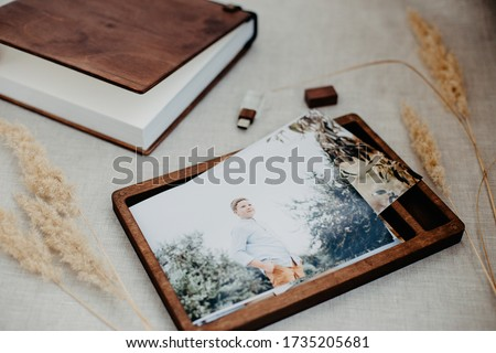 Luxury wooden photo book, wooden box with summer photos printed and flash card on linen natural background. Family memories photobook. Save your summer vacation memories. Photo album with wooden cover