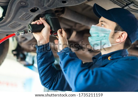 Mechanician changing car wheel in auto repair shop wearing a mask, coronavirus concept Royalty-Free Stock Photo #1735211159