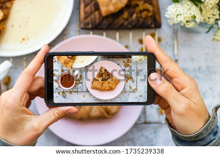 Make picture of vegan food with phone. Smartphone blogging photography of apple pie.