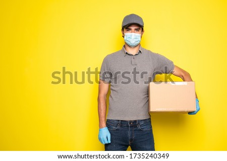 delivery man wearing medical protection against infection, carrying a package on grey background #1735240349