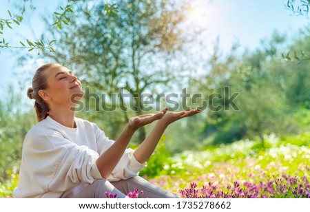 Nice happy woman sitting on flowers meadow in the garden, enjoying bright spring sunshine, active spring holidays in countryside Royalty-Free Stock Photo #1735278662