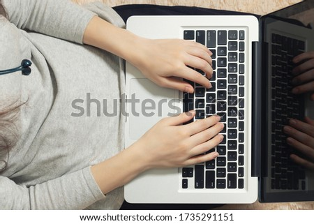 Girl working on a laptop at home on the couch. Freelance and Remote Quarantine Concept, top view