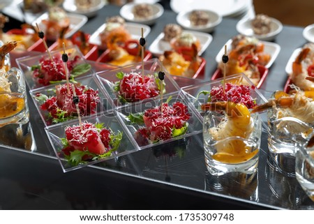 Slices of tuna sprinkled with grated boiled beets, decorated with lettuce. Beautiful skewers, serve on small transparent plates. Beautiful back light. #1735309748