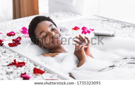 Smiling and relaxing african american woman with closed eyes takes bath with foam and petals Royalty-Free Stock Photo #1735323095