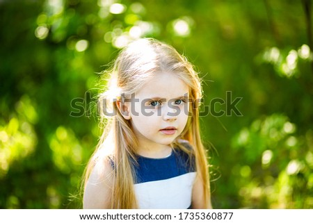 Close-up portrait of a girl child with blurry background on a summer sunny day with long blonde hair looking at the frame