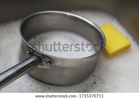 A stainless steel pot inside a kitchen sink which contains soapy water. Washing dishes concept image.