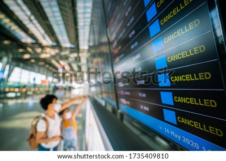 Asian female traveler looking on  flights information board in airport and it show flights cancellation status on because coronavirus or covid-19 pandemic effected. airline business crisis concept Royalty-Free Stock Photo #1735409810