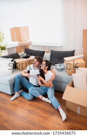 Young happy couple drinking wine, celebrating moving to new home and sitting among boxes. Vertical photo