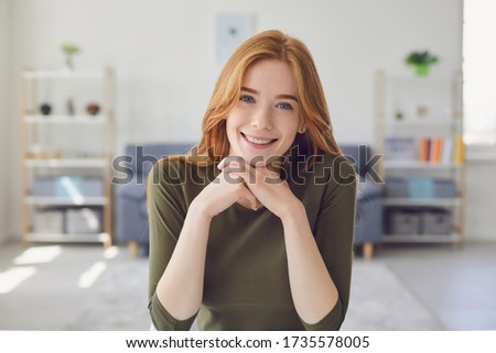Online video call. Headshot of a happy girl looking at the camera smiling listening to friends sitting at home. Royalty-Free Stock Photo #1735578005