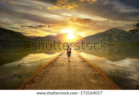 Traveler walking along the road to the mountains. Royalty-Free Stock Photo #173564057