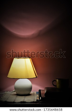 amazing view of room interior with night lamp, books and tea cup