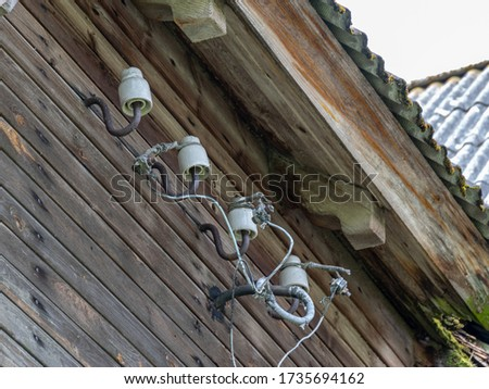 picture with electric wires, detail from an old wooden barn, a fragment of a wooden roof