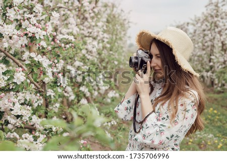 Nature Photographer taking pictures outdoors. Beautiful girl in a hat and dress in an apple orchard. Open air outside the city. Stylish woman between flowering trees with a camera.