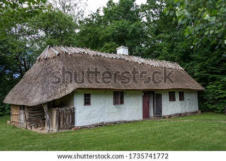 Traditional country house with thatched roof. Rural theme. Frilandsmuseet, Denmark. Royalty-Free Stock Photo #1735741772