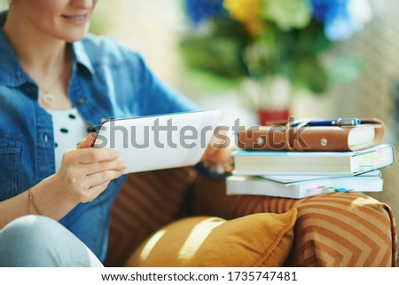Closeup on smiling woman in jeans shirt with tablet PC study online in the living room in sunny day. Royalty-Free Stock Photo #1735747481