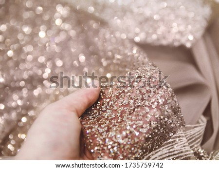 Hand holding gold blush glitter fabric to show it fr somebody. Close up picture of rose doll glitter tulle with sparkles on background, greeting card for holiday or celebration, wallpaper with decor