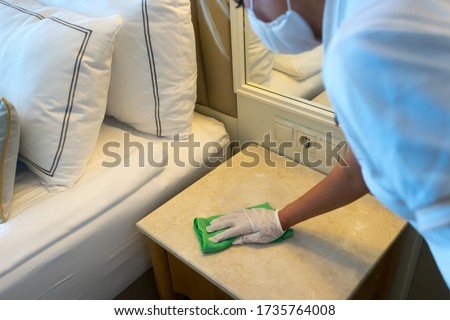 Deep cleaning for Covid-19 (corona virus) disease prevention. For safety, spray alcohol, disinfectant on the cleaning cloth wipes in places that are frequently touched at the hotel. Royalty-Free Stock Photo #1735764008