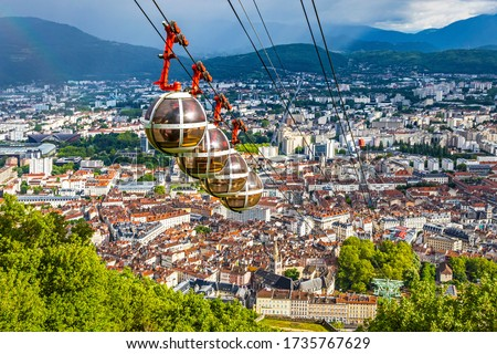 Picturesque aerial view of Grenoble city, Auvergne-Rhone-Alpes region, France. Grenoble-Bastille cable car on the foreground. French Alps on the background Royalty-Free Stock Photo #1735767629