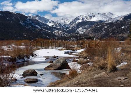 A beautiful winter day with a view of a stream flowing towards the snow capped Rocky Mountains in Rocky Mountain National Park near Estes Park, Colorado #1735794341