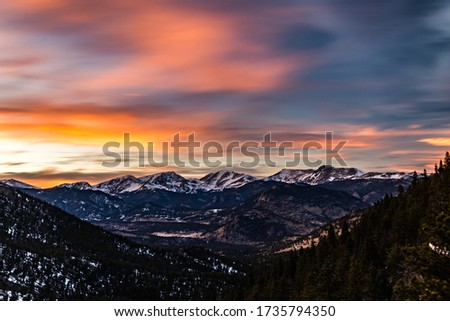 A beautiful sunset sky with colorful dusk clouds sweeping over the snow capped Rocky Mountains on a cold, winter evening in Rocky Mountain National Park near Estes Park, Colorado #1735794350