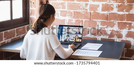 Young Asian businesswoman work at home and virtual video conference meeting with colleagues business people, online working, video call due to social distancing at home office Royalty-Free Stock Photo #1735794401
