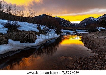 A beautiful sunset, dusk sky with a flowing river running through a valley with a view of the Rocky Mountains in the distance near Estes Park, Colorado #1735796039