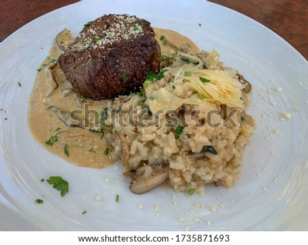 Medium rare filet mignon on top of a mushroom sauce accompanied with mushroom risotto.
