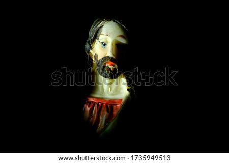 Light falling on a figure of Jesus Christ on a plaque depicting the Last Supper, as he contemplates the events about to happen during the last meal with his disciples. Portrait of Jesus, closeup view.
