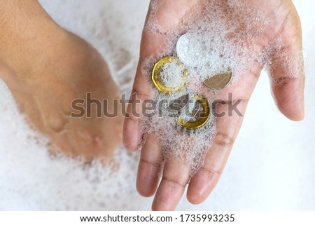 Lady hands cleaning Singapore coins money with soap foam to prevent the spread of bacteria and viruses. Anti Corona virus Covid-19 ptotective concept, new normal concept Royalty-Free Stock Photo #1735993235
