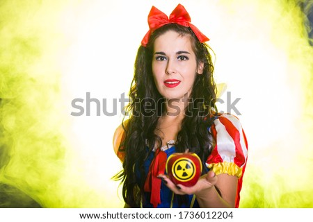 Woman dressed as fairytale character holds Radioactive atomic nuclear ionizing radiation danger warning symbol on apple. Nuclear and radiation measurement concept.
