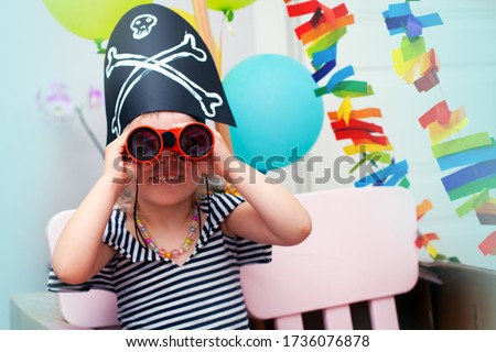 A little girl in a pirate costume looks through binoculars directly at the camera. Birthday in the style of pirates. A child in a pirate hat smiles and looks at the camera, close-up.