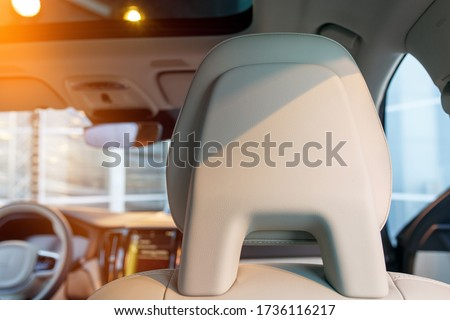 A close up view of car seat headrest. White leather interior of a new modern car, evening sun coming through the window. Royalty-Free Stock Photo #1736116217