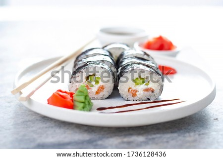 Sushi Rolls asian food stylish beautiful close up picture. Tasty delishes meals with rice and seafood on the white plate and light gray table with ginger and wasabi closeup view beautiful picture