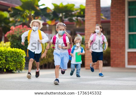 School child wearing face mask during corona virus and flu outbreak. Boy and girl going back to school after covid-19 quarantine and lockdown. Group of kids in masks for coronavirus prevention.  #1736145332