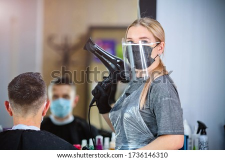 A hairdresser with security measures for Covid-19 holding a hairdryer and looking at the camera in a medicine mask, social distance, cutting hair with a medical mask, eye mask and rubber gloves  Royalty-Free Stock Photo #1736146310
