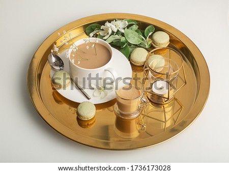 Breakfast is served with flowers,  cup of coffee and dessert. Interior of the living room with a coffee table. A Cup of coffee on a gold tray, a candle. Still life with home interior and comfor #1736173028