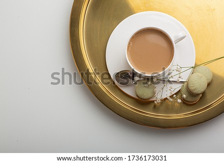 Breakfast is served with flowers,  cup of coffee and dessert. Interior of the living room with a coffee table. A Cup of coffee on a gold tray, a candle. Still life with home interior and comfor #1736173031