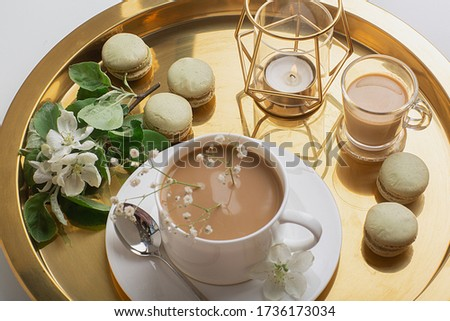 Breakfast is served with flowers,  cup of coffee and dessert. Interior of the living room with a coffee table. A Cup of coffee on a gold tray, a candle. Still life with home interior and comfor #1736173034